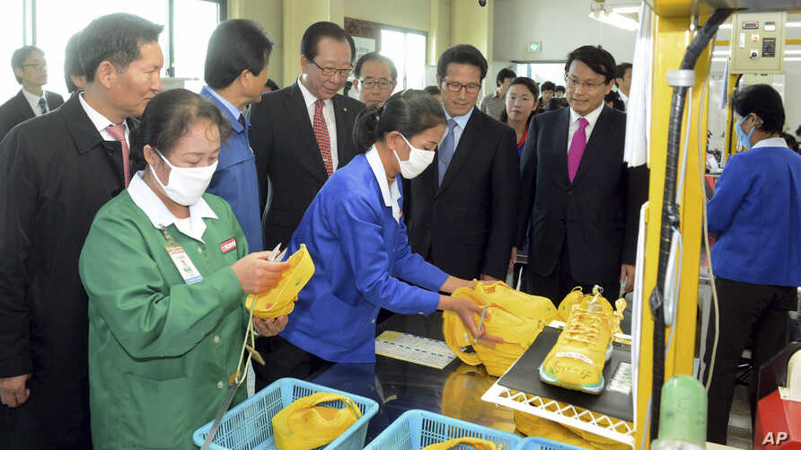 Ahn Hong-joon, chairman of the South Korean National Assembly's Foreign Affairs and Unification Committee and lawmakers look at North Korean workers during their visit to a factory in the inter-Korean industrial park in Kaesong, North Korea, Oct. 30,