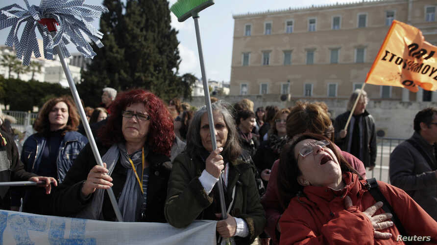 Cleaning ladies in the public sector shout slogans during a rally outside the parliament in Athens, March 12, 2014.