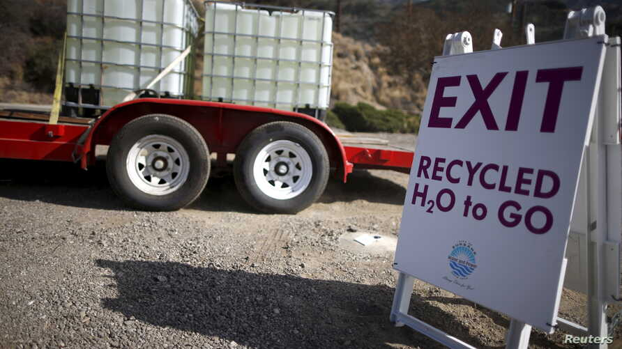 FILE - Gary Sutliff, 73, drives away after filling up water tanks with recycled water to revive dying plants in his garden, in Burbank, Los Angeles, California, United States, Sept. 12, 2015. The city has set up a five-spigot filling station to give