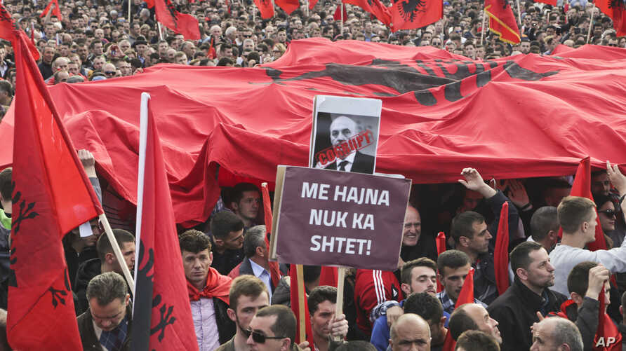 """Kosovo opposition supporters wave Albanian flags during an anti-government rally in Kosovo's capital Pristina, Feb. 17, 2016. The banner in Albanian reads """"Corrupt - with thieves there is no country."""""""