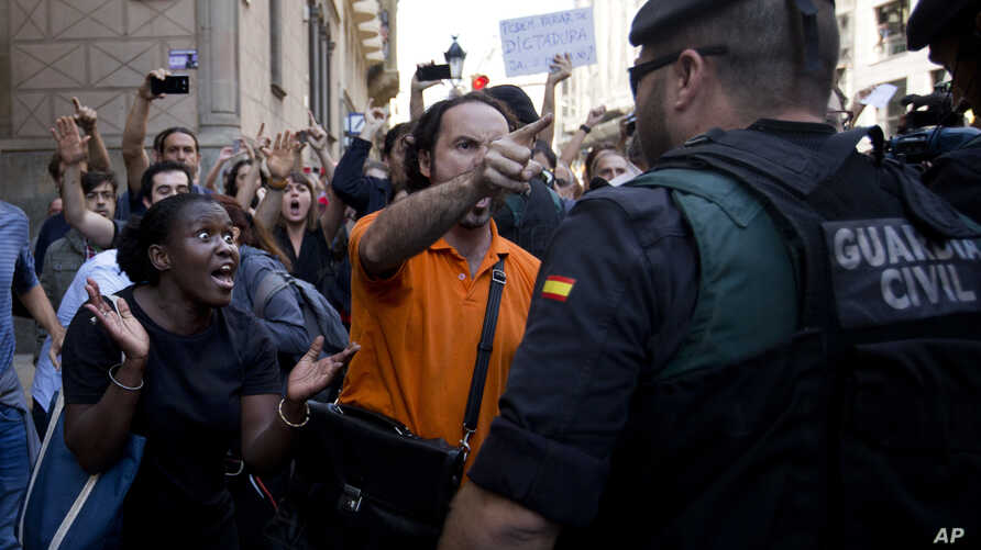 Demonstrators react as they try to stop the car carrying Xavier Puig, a senior at the Department of External Affairs, Institutional Relations and Transparency of the Catalan Government office, after he was arrested by Guardia Civil officers in Barcel