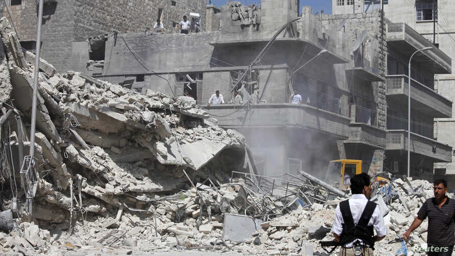Civilians and members of the Free Syrian Army inspect a damaged building in al-Kalaseh neighbourhood in  Aleppo, after a morning jet air strike, September 19, 2012.