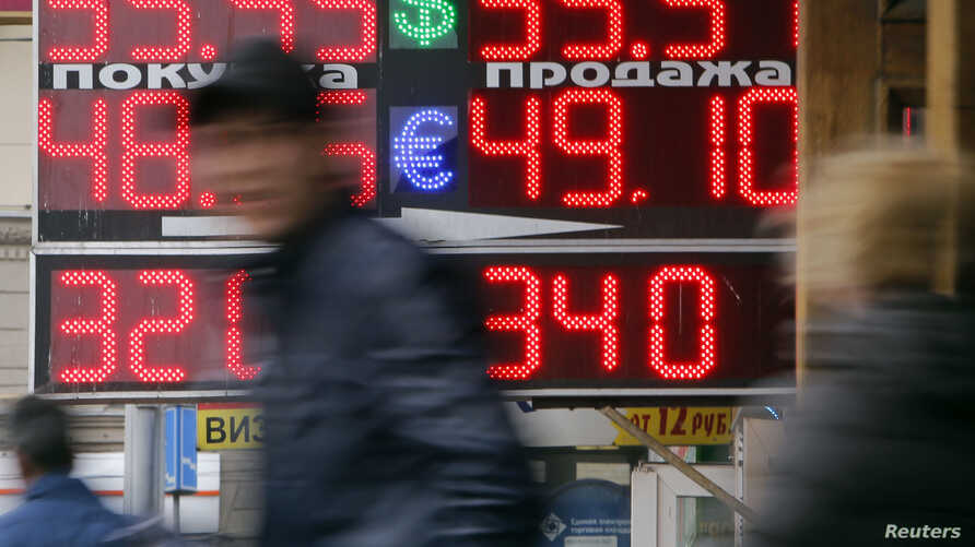 People pass by a board displaying exchange currency rates in Moscow, Russia, April 3, 2014.