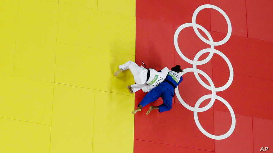 Brazil's Rafaela Silva, blue, and Mongolia's Sumiya Dorjsuren compete during the final of the women's 57 kg judo competition at the 2016 Summer Olympics in Rio de Janeiro, Brazil, Aug. 8, 2016.