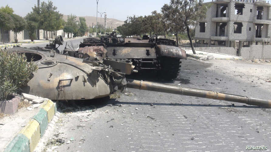 A destroyed Syrian army tank is seen in the Damascus suburb of al-Tel July 28, 2012.