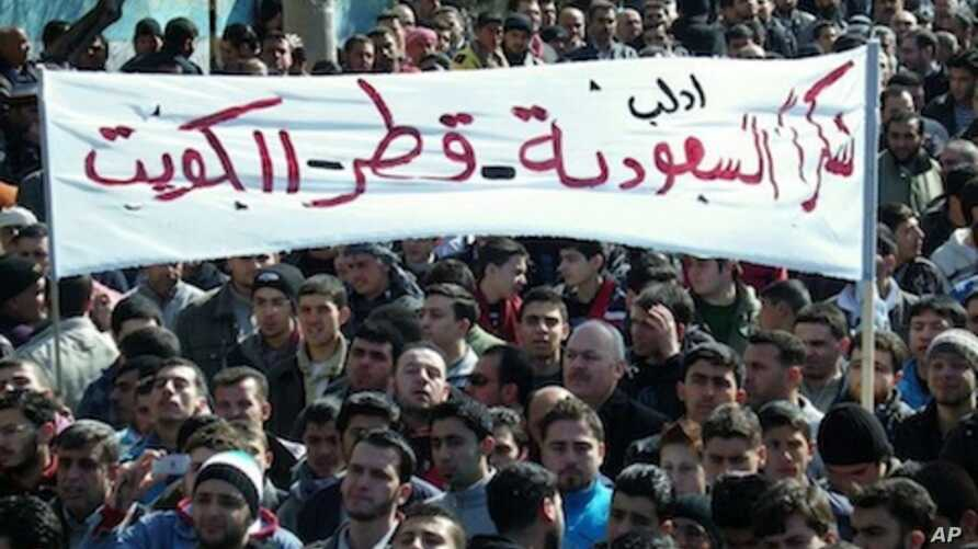 "In this Friday, March 2, 2012 citizen journalism image provided by the Local Coordination Committees in Syria, anti-Syrian regime protesters hold up a banner in Arabic reading: ""thank you Saudi Arabia, Qatar and Kuwait,"" during a demonstration, in Id"