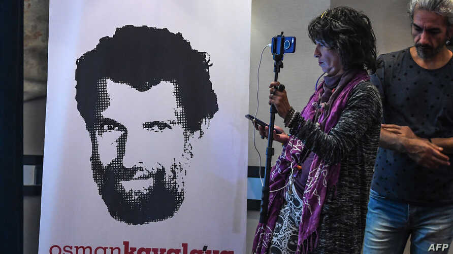 A journalist stands in front of a poster featuring jailed businessman and philanthropist Osman Kavala during a press conference held by his lawyers, Oct. 31, 2018.