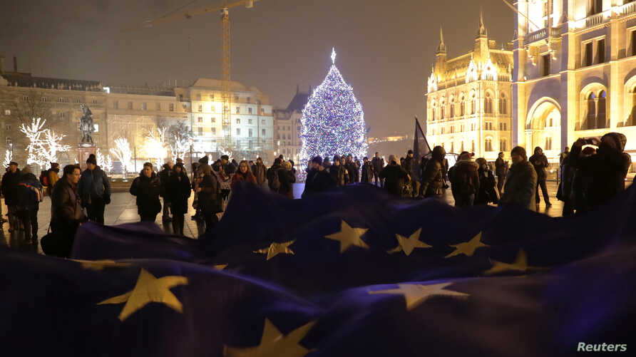 """People hold a big European Union flag during a protest against a proposed new labor law, billed as the """"slave law,"""" in front of the Parliament building in Budapest, Hungary, Dec. 18, 2018."""