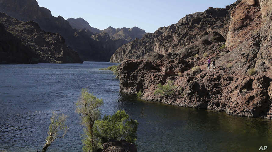 FILE - Hikers make their way along the banks of the Colorado River near Willow Beach, Arizona, April 14, 2013.