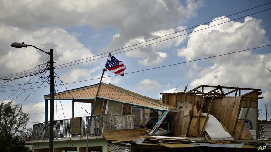 A political party banner waves over a home damaged in the passing of Hurricane Maria, in the community of Ingenio in Toa Baja, Puerto Rico, Oct. 2, 2017. President Donald Trump is planning to visit the U.S. territory on Tuesday.