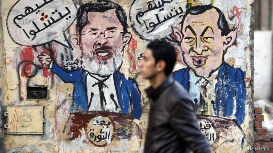 A protester walks past a graffiti during a march at Tahrir Square in Cairo, February 11, 2013. The march, was organized by Egyptians who oppose Egypt's President Mohamed Morsi and members of the ruling Muslim Brotherhood on the second anniversary of