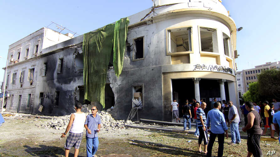 People gather to look at the site of a car bombing in Benghazi, Libya, Sept. 11, 2013.