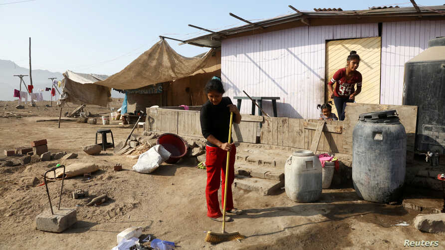 A woman cleans her home in Villa Maria del Triunfo, a shanty town on the outskirts of Lima, Peru, May 9, 2017.