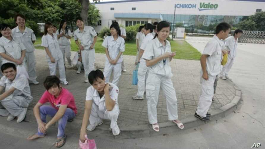 Chinese workers stand outside the Ichikoh Valeo factory, a Japanese-owned plant that makes head lamps and fog lights for the auto industry, in Foshan, southern China's Guangdong province, 18 Jun 2010
