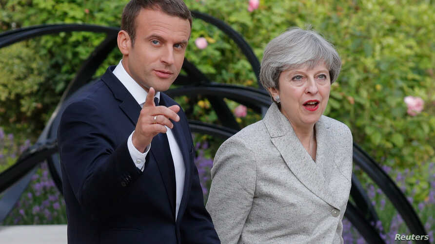 French President Emmanuel Macron escorts Britain's Prime Minister Theresa May as they arrive to speak to the press at the Elysee Palace in Paris, France, June 13, 2017.