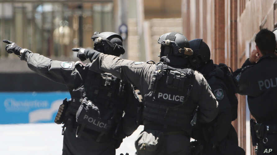 Armed police officers point as they stand at the ready close to a cafe under siege at Martin Place in Sydney, Australia, Dec. 15, 2014.