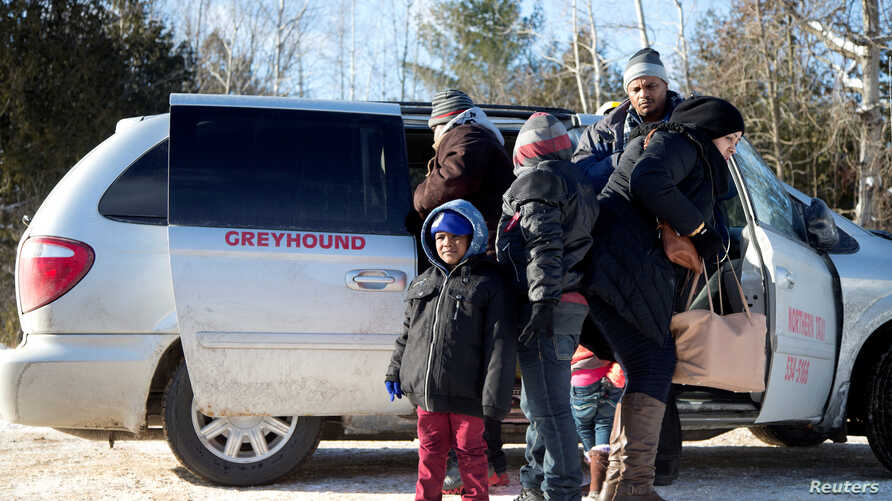 FILE - A family which claimed to be from Sudan, piles out of a Northern Taxi which drove them to the U.S.-Canada border in Champlain, New York, February 17, 2017.