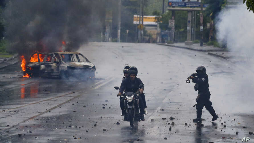 A police officer aims his shotgun at two men riding a motorcycle during a protest against Nicaragua's President Daniel Ortega in Managua, Nicaragua, Monday, May 28, 2018.