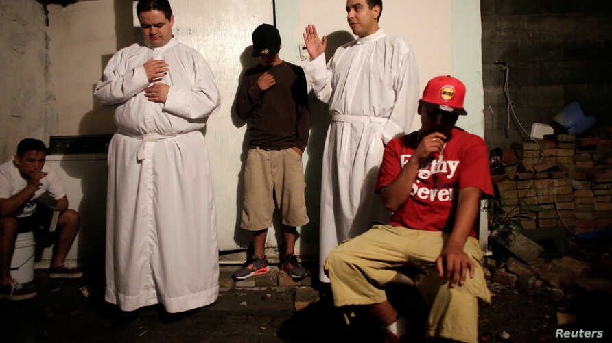 FILE - Aspiring Catholic priests Jose Luis Guerra (L) and Jose Luis Fernandez, members of Raza Nueva in Christ, a project of the archdiocese of Monterrey, bless young men during a visit to a neighborhood in the municipality of Garcia, on the outskirt