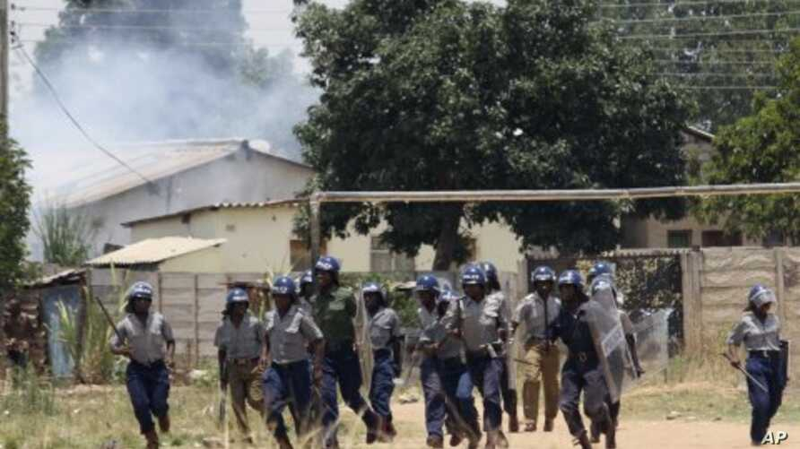 Police leave the scene after throwing teargas at a house in Chitungwiza, Zimbabwe, November 6, 2011.