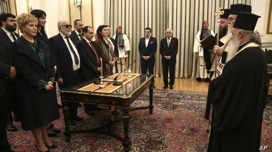 Greece Cabinet Reshuffle: Newly appointed ministers and deputy ministers take an oath as Greek President Prokopis Pavlopoulos, center right, and Prime Minister Alexis Tsipras, center left, look on, during a swearing in ceremony at the Presidential pa