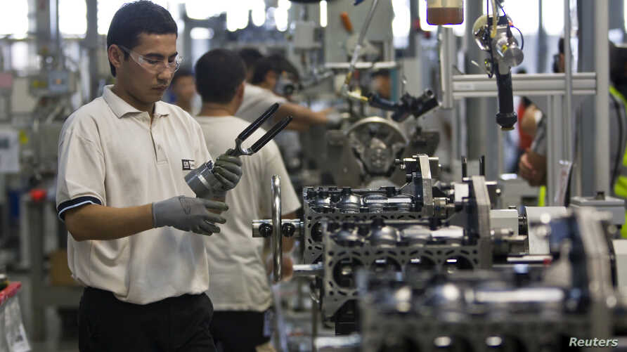 Employees work on an assembly line at the General Motors Powertrain-Uzbekistan plant  in Tashkent August 31, 2012. Ninety-four percent of new cars sold in Uzbekistan last year were made by General Motors - the biggest share of any market served by th
