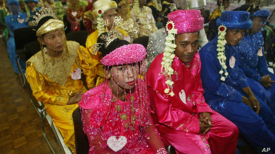 Indonesian couples wait for their turn to wed during a 47-couple mass wedding ceremony in Jakarta, Indonesia, which was aimed at helping those couples unable to afford proper weddings, May 18, 2005.