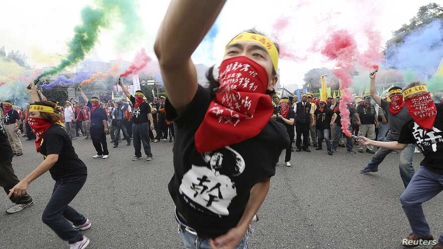 People throw smoke grenades during the annual Labor Day protest in front of the Presidential Office in Taipei, Taiwan, May 1, 2015.