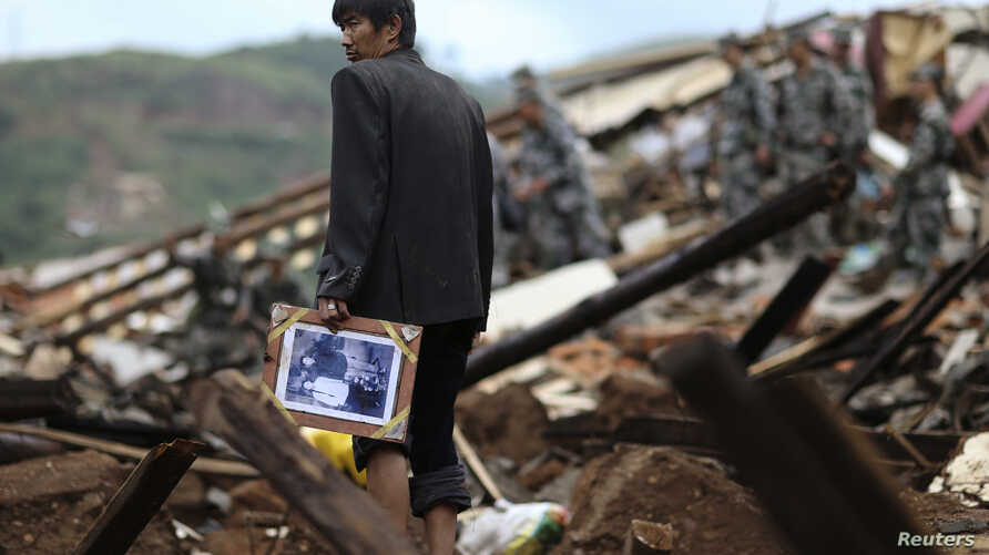 A man carries a picture as he stands among debris in the Longtoushan township of Ludian county, Yunnan province August 4, 2014