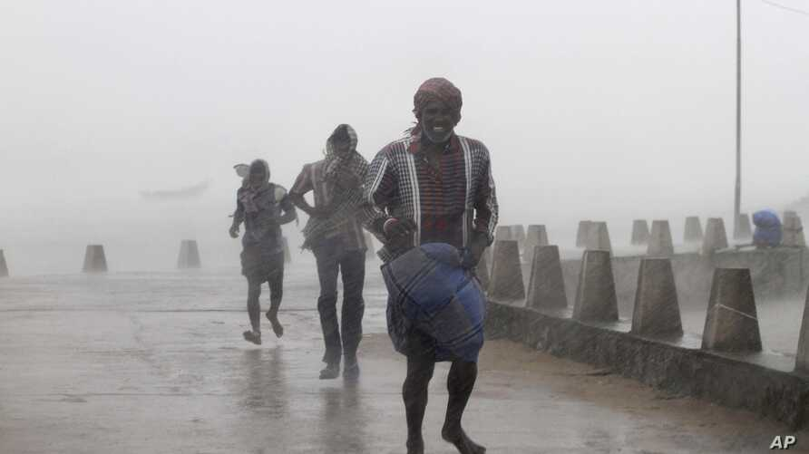 People run for shelter as heavy rain and wind gusts rip through the Bay of Bengal coast at Gopalpur, Orissa, about 285 kilometers (178 miles) north east of Visakhapatnam, India, Sunday, Oct. 12, 2014.