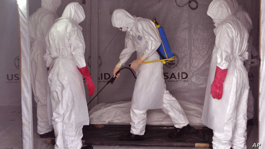 Health workers wearing protective gear spray the shrouded body of a man with disinfectant as they suspect he died from the Ebola virus, at a USAID, American aid Ebola treatment center at Tubmanburg on the outskirts of Monrovia, Liberia, Nov. 28, 2014