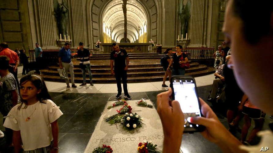 People stand around the tomb of former Spanish dictator Francisco Franco inside the basilica at the the Valley of the Fallen monument near El Escorial, outside Madrid, Spain, Aug. 24, 2018.