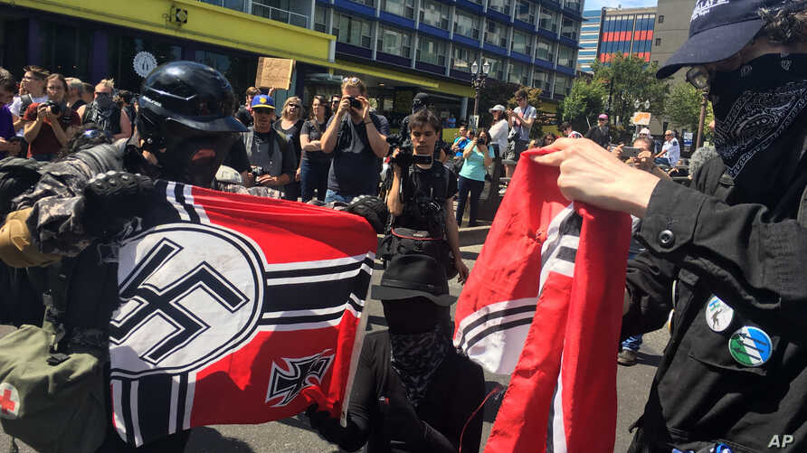 Counterprotesters tear a Nazi flag, Aug. 4, 2018 in Portland, Ore. Small scuffles broke out as police dispersed hundreds of right-wing and self-described anti-fascist protesters.