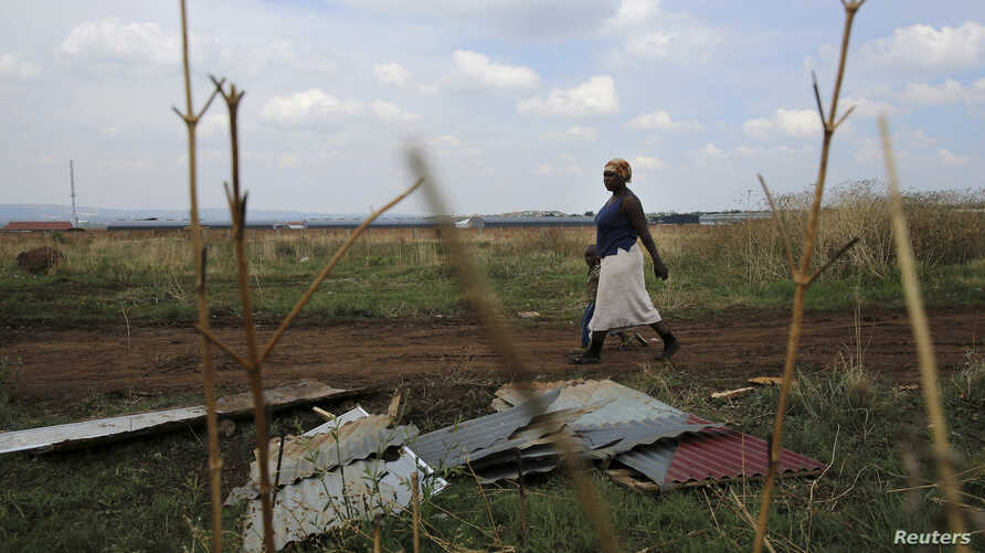 FILE - A mother and child walk past corrugated iron left by residents who intended to build an informal settlement at an open land in Nellmapius township, 20 km (12 miles) east of Pretoria.