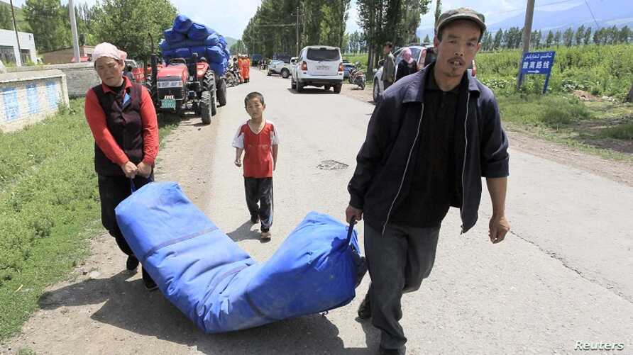 Uighur residents carry a temporary tent being distributed by the rescue team after an earthquake, in Nalati township, Xinjiang Uighur Autonomous Region June 30, 2012.
