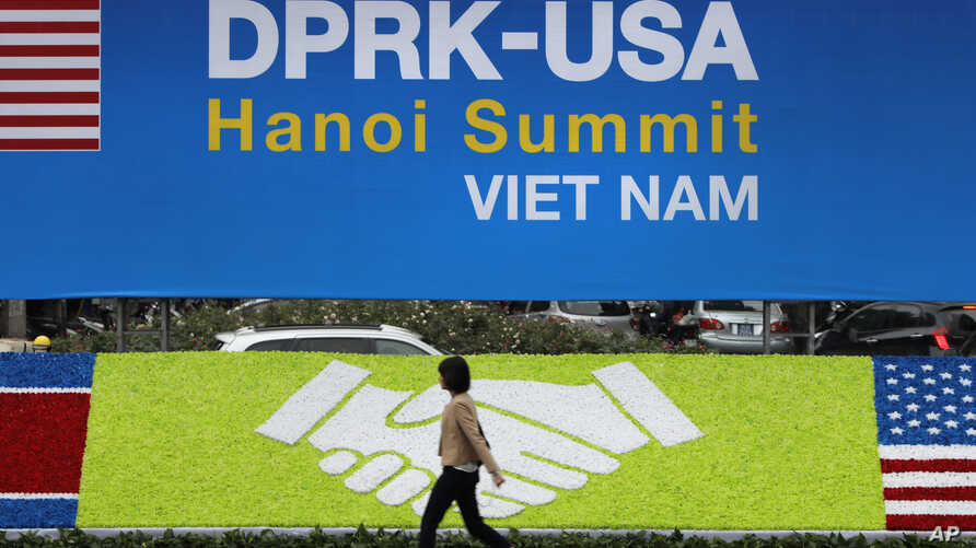 A woman walks past banners for the U.S and North Korean summit at the International Media Center in Hanoi, Vietnam, Feb. 25, 2019.