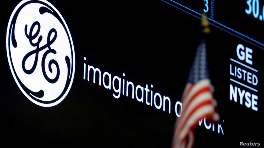 FILE - The ticker and logo for General Electric Co. is displayed on a screen at the post where it's traded on the floor of the New York Stock Exchange (NYSE) in New York City, June 30, 2016.