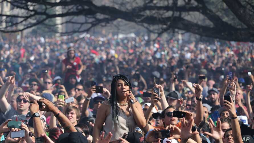 FILE - Partygoers listen to live music on the second of two days at the annual 4/20 marijuana festival in Denver, April 20, 2014. Colorado is now one of four states in the United States that allows recreational use of marijuana.