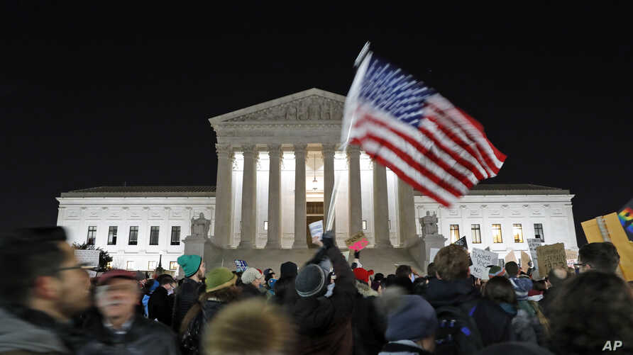 FILE - a protester waves an American flag in front of the Supreme Court during a protest about President Donald Trump's recent executive orders in Washington.