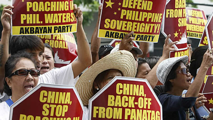 Protesters display placards during their rally outside the Chinese Consulate at the financial district of Makati city, east of Manila, Philippines, April 16, 2012.