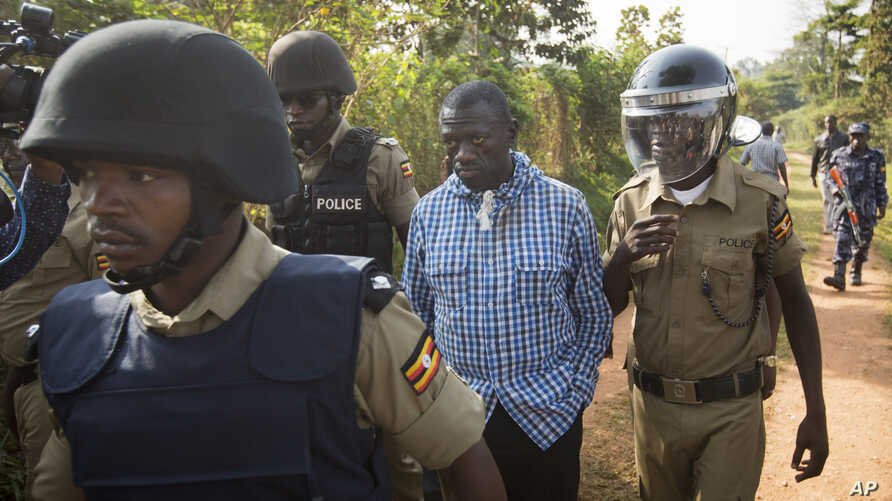 Uganda's main opposition leader Kizza Besigye, center, is arrested by police and thrown into the back of a blacked-out police van which whisked him away and was later seen at a rural police station, outside his home in Kasangati, Uganda Monday, Feb.