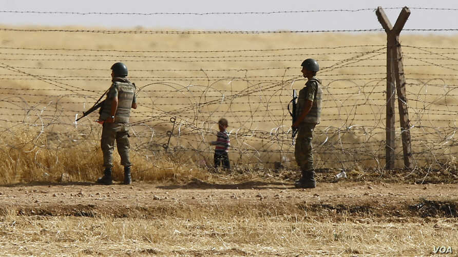 FILE - Turkish soldiers stand guard as a Syrian refugee boy waits behind border fences to cross into Turkey on the Turkish-Syrian border, near the southeastern town of Akcakale in Sanliurfa province, Turkey, June 5, 2015.