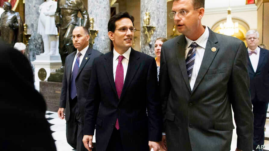 House Majority Leader Eric Cantor (r), walks with Rep. Doug Collins, after the final votes of the week in the House, June 12, 2014.