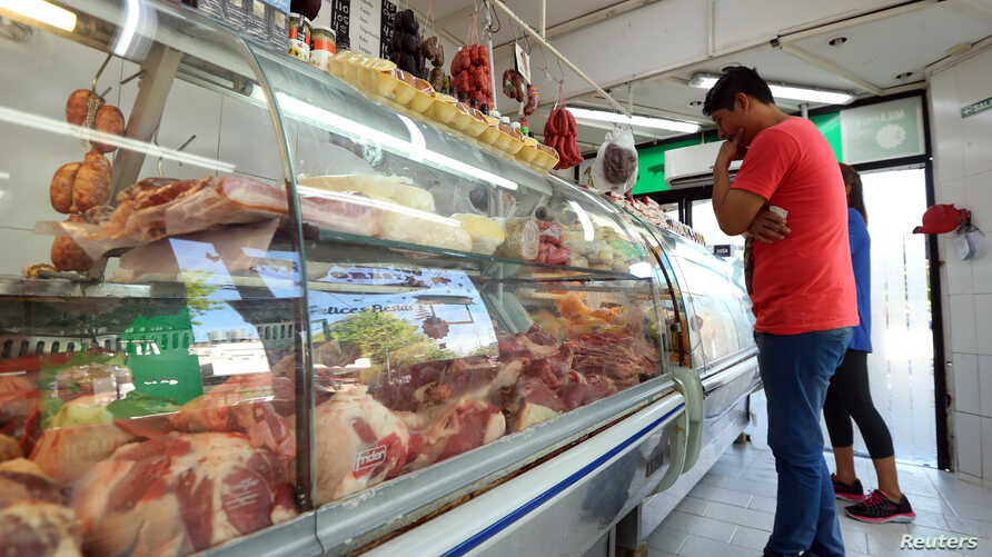 A man looks at meat on display inside a butcher shop in Buenos Aires, Argentina October 29, 2018. Picture taken October 29, 2018.