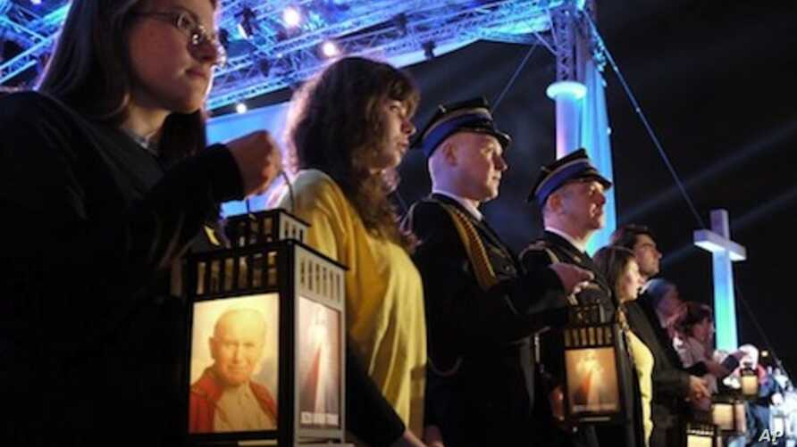 Faithful in Warsaw, Poland hold lanterns with an image of Pope John Paul II as they attend a prayer vigil honoring the late Pontiff on the eve of his beatification, Saturday, April 30, 2011.