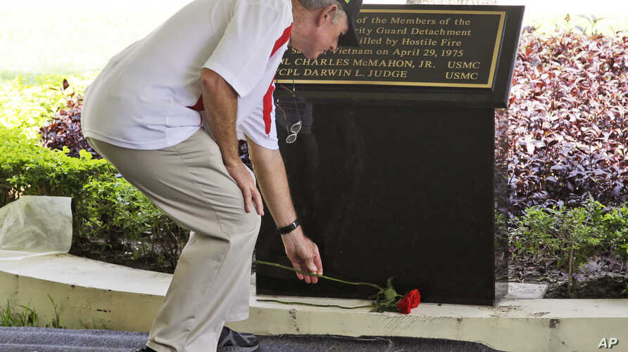 Former U.S. Marine Sgt. Kevin Maloney of Hollywood, Florida, places a flower in front of the plaque dedicated to his fallen comrades Cpl. Charles McMahon and Lance Cpl. Darwin Judge who were the last U.S. servicemen killed in the Vietnam War, during