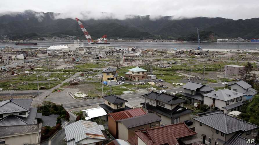 FILE - Undamaged homes are seen on a hillside in the foreground as a tsunami damaged area is seen behind in the  town of Ofunato, in northeast Japan, Monday, Sept. 5, 2011.