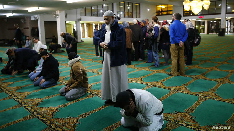 FILE - Men pray as visitors are given a tour of the Birmingham Central Mosque, on visit my mosque day in Birmingham, Feb. 7, 2016.