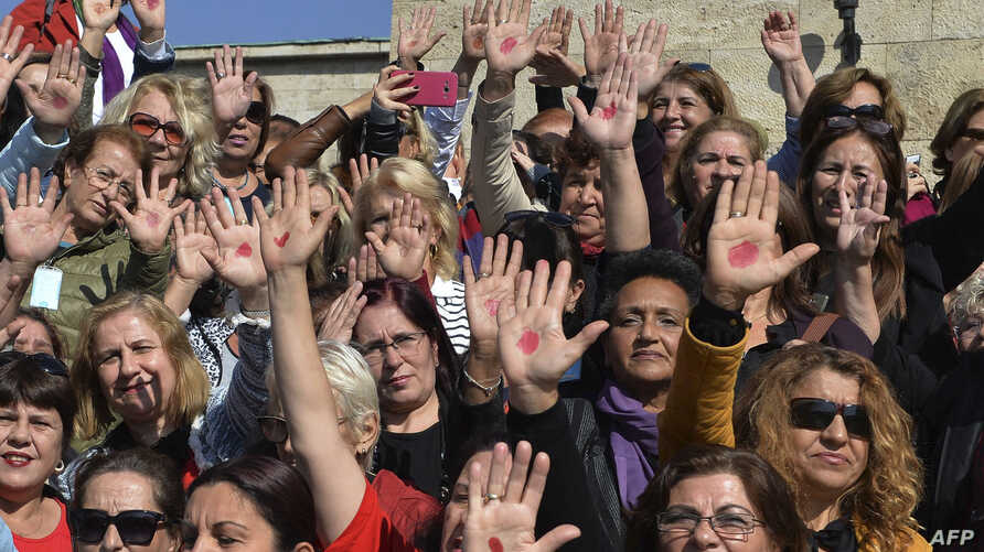 Turkish women with a red point painted on their hand, gather outside the Turkish parliament to protest against a draft law granting muftis the right to register marriage contracts, in Ankara, Oct. 12, 2017.