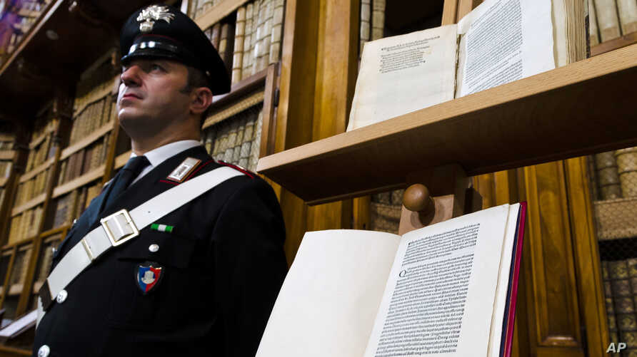 A Carabinieri policeman stands, Wednesday, May 18, 2016, next to a book, bottom, reproducing a letter written by Christopher Columbus in 1493 about his discovery of the New World that had been replaced at Florence's Riccardiana library with a forgery